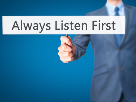 Always Listen First - Businessman hand holding sign. Business, technology, internet concept. Stock Photo