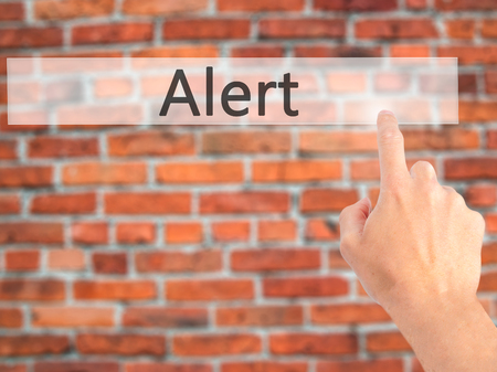 Alert - Hand pressing a button on blurred background concept . Business, technology, internet concept. Stock Photo Stock Photo