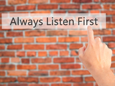 always listen first: Always Listen First - Hand pressing a button on blurred background concept . Business, technology, internet concept. Stock Photo