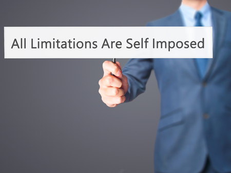 imposed: All Limitations Are Self Imposed - Businessman hand holding sign. Business, technology, internet concept. Stock Photo Stock Photo