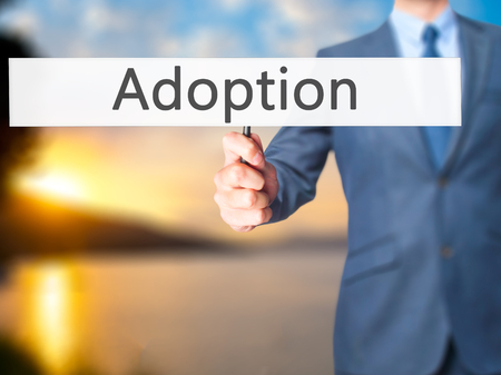mother in law: Adoption - Businessman hand holding sign. Business, technology, internet concept. Stock Photo Stock Photo