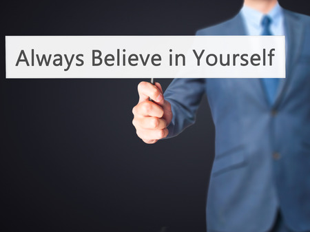 triumphant: Always Believe in Yourself - Businessman hand holding sign. Business, technology, internet concept. Stock Photo Stock Photo