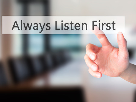Always Listen First - Hand pressing a button on blurred background concept . Business, technology, internet concept. Stock Photo