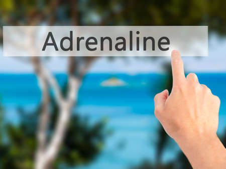 adrenaline: Adrenaline - Hand pressing a button on blurred background concept . Business, technology, internet concept. Stock Photo