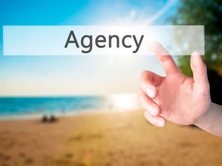 Agency - Hand pressing a button on blurred background concept . Business, technology, internet concept. Stock Photo Stock Photo