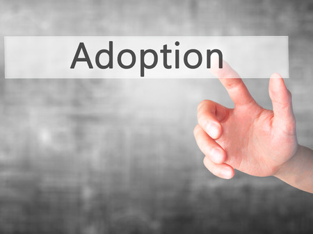 adopting: Adoption - Hand pressing a button on blurred background concept . Business, technology, internet concept. Stock Photo Stock Photo
