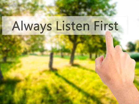 Siempre escuchar primero - mano presionando un botón en concepto de fondo borroso. Negocios, la tecnología, el concepto de internet. Foto de stock Foto de archivo