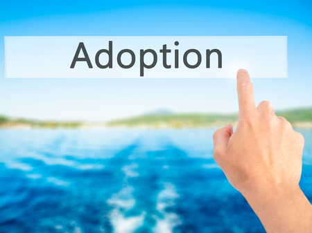 daughter in law: Adoption - Hand pressing a button on blurred background concept . Business, technology, internet concept. Stock Photo Stock Photo