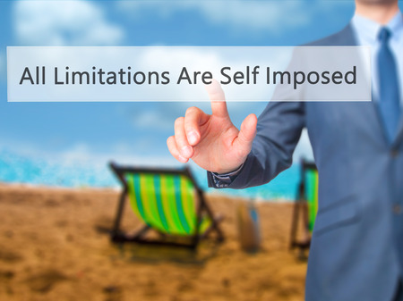 imposed: All Limitations Are Self Imposed - Businessman press on digital screen. Business,  internet concept. Stock Photo