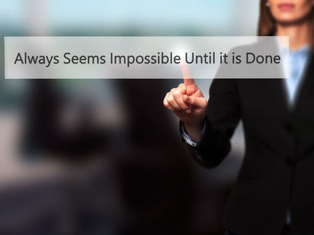 unachievable: Always Seems Impossible Until it is Done - Isolated female hand touching or pointing to button. Business and future technology concept. Stock Photo