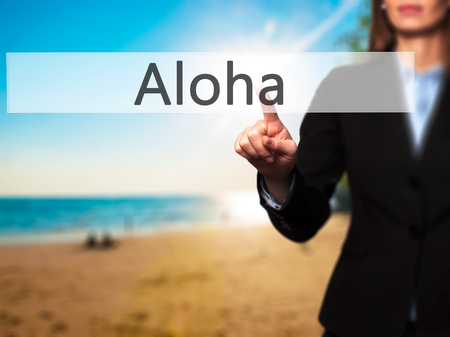 Aloha - Isolated female hand touching or pointing to button. Business and future technology concept. Stock Photo