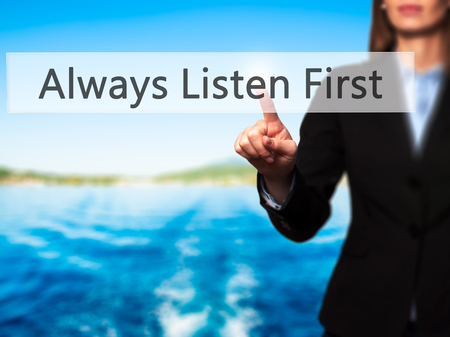 always listen first: Always Listen First - Isolated female hand touching or pointing to button. Business and future technology concept. Stock Photo Stock Photo