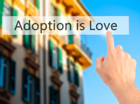 son in law: Adoption is Love - Hand pressing a button on blurred background concept . Business, technology, internet concept. Stock Photo Stock Photo