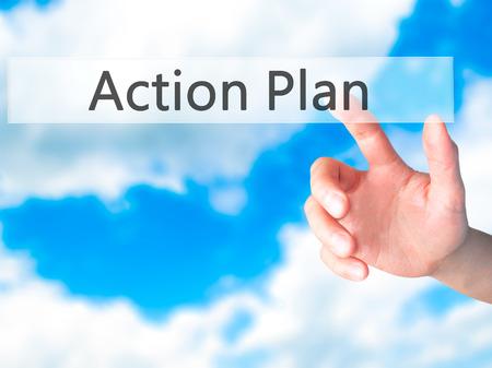 Actieplan - Hand indrukken van een knop op onscherpe achtergrond concept. Business, technologie, internet concept. Stock foto