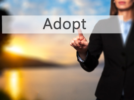 guardianship: Adopt - Isolated female hand touching or pointing to button. Business and future technology concept. Stock Photo