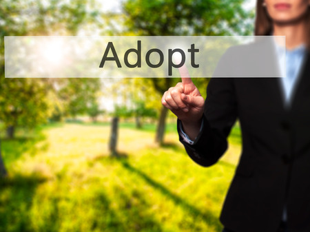 adopting: Adopt - Isolated female hand touching or pointing to button. Business and future technology concept. Stock Photo
