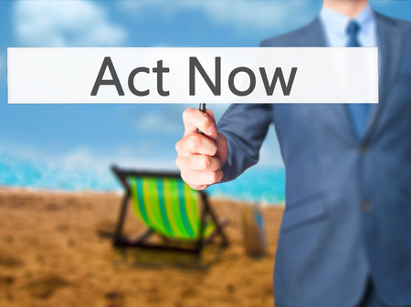 Act Now - Business man showing sign. Business, technology, internet concept. Stock Photo