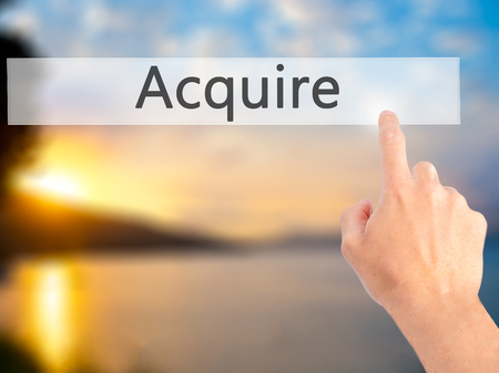 acquire: Acquire - Hand pressing a button on blurred background concept . Business, technology, internet concept. Stock Photo Stock Photo