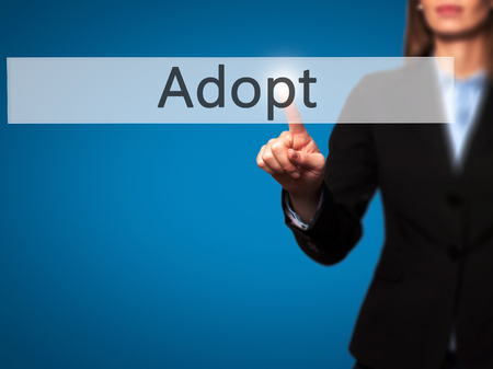 foster parenting: Adopt - Isolated female hand touching or pointing to button. Business and future technology concept. Stock Photo