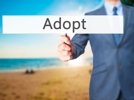 Adopt - Business man showing sign. Business, technology, internet concept. Stock Photo