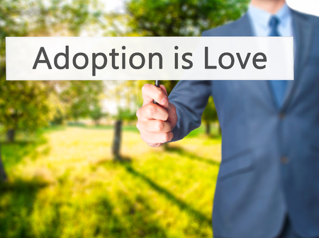 son in law: Adoption is Love - Business man showing sign. Business, technology, internet concept. Stock Photo Stock Photo