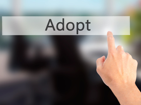 adopting: Adopt - Hand pressing a button on blurred background concept . Business, technology, internet concept. Stock Photo Stock Photo