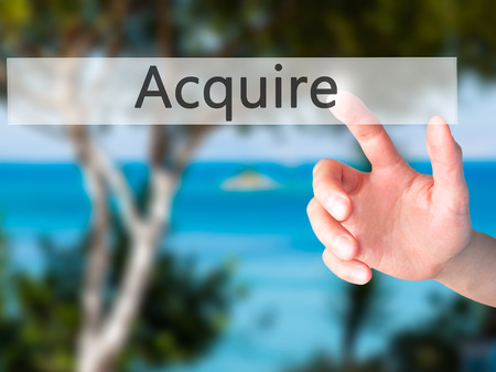 Acquire - Hand pressing a button on blurred background concept . Business, technology, internet concept. Stock Photo Stock Photo