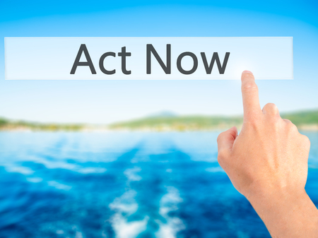 Act Now - Hand pressing a button on blurred background concept . Business, technology, internet concept. Stock Photo