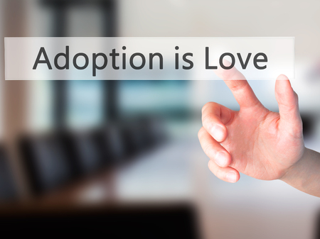 adopting: Adoption is Love - Hand pressing a button on blurred background concept . Business, technology, internet concept. Stock Photo Stock Photo