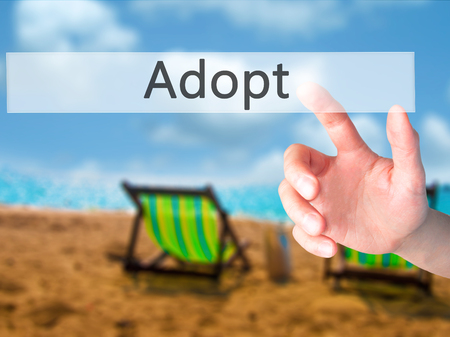 guardianship: Adopt - Hand pressing a button on blurred background concept . Business, technology, internet concept. Stock Photo Stock Photo