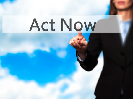 Act Now - Isolated female hand touching or pointing to button. Business and future technology concept. Stock Photo