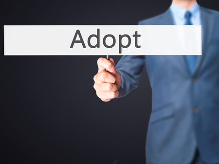 mother in law: Adopt - Business man showing sign. Business, technology, internet concept. Stock Photo