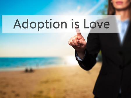 adopting: Adoption is Love - Isolated female hand touching or pointing to button. Business and future technology concept. Stock Photo