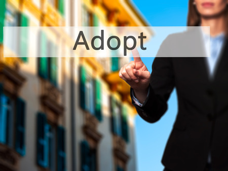 Adopt - Isolated female hand touching or pointing to button. Business and future technology concept. Stock Photo