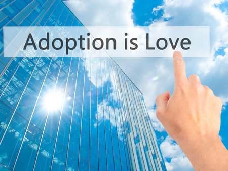 foster parenting: Adoption is Love - Hand pressing a button on blurred background concept . Business, technology, internet concept. Stock Photo Stock Photo