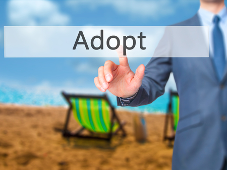 foster parenting: Adopt - Businessman press on digital screen. Business,  internet concept. Stock Photo Stock Photo