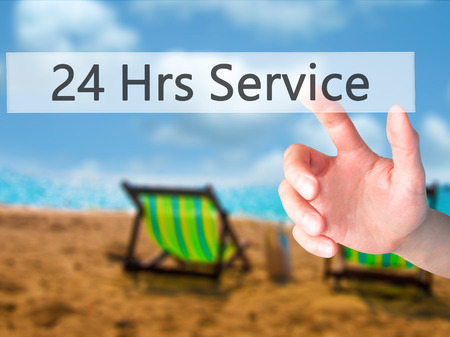 24 Hrs Service - Hand pressing a button on blurred background concept . Business, technology, internet concept. Stock Photo Stock Photo