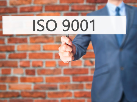 certify: ISO 9001 - Businessman hand holding sign. Business, technology, internet concept. Stock Photo
