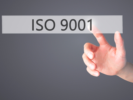 certify: ISO 9001 - Hand pressing a button on blurred background concept . Business, technology, internet concept. Stock Photo