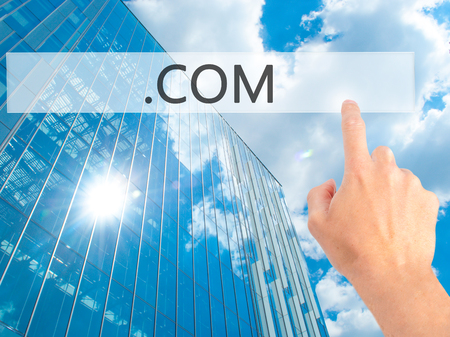 domain: .COM - Hand pressing a button on blurred background concept . Business, technology, internet concept. Stock Photo