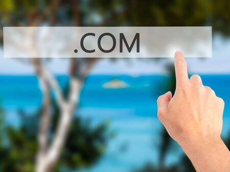 suffix: .COM - Hand pressing a button on blurred background concept . Business, technology, internet concept. Stock Photo