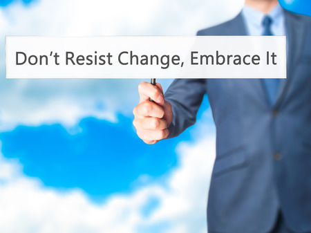 personal decisions: Dont Resist Change, Embrace It! - Businessman hand holding sign. Business, technology, internet concept. Stock Photo Stock Photo