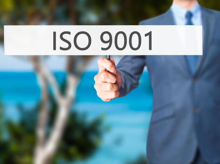 ISO 9001 - Businessman hand holding sign. Business, technology, internet concept. Stock Photo