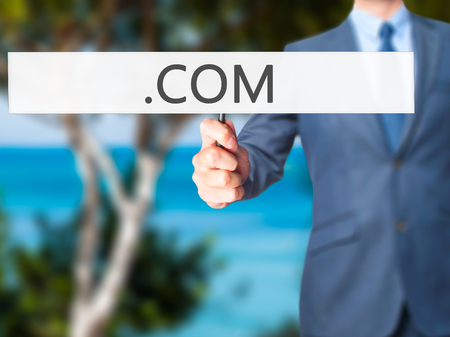domain: .COM - Businessman hand holding sign. Business, technology, internet concept. Stock Photo