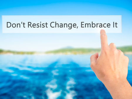 Dont Resist Change, Embrace It! - Hand pressing a button on blurred background concept . Business, technology, internet concept. Stock Photo Stock Photo