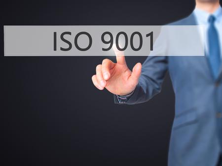 certify: ISO 9001 - Businessman hand pressing button on touch screen interface. Business, technology, internet concept. Stock Photo