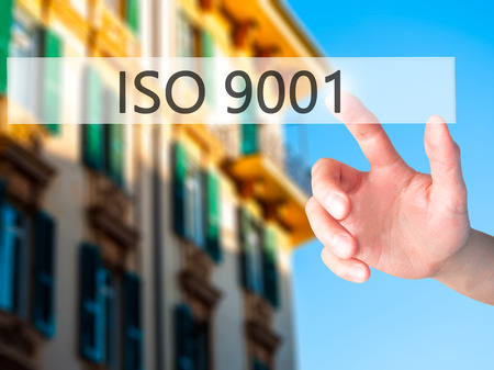 standardization: ISO 9001 - Hand pressing a button on blurred background concept . Business, technology, internet concept. Stock Photo