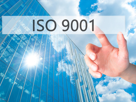 ISO 9001 - Hand pressing a button on blurred background concept . Business, technology, internet concept. Stock Photo