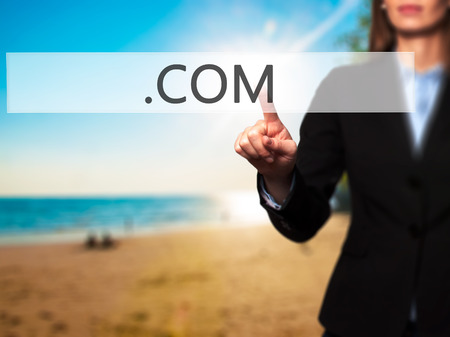 suffix: .COM - Businesswoman hand pressing button on touch screen interface. Business, technology, internet concept. Stock Photo Stock Photo