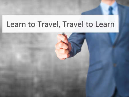 Learn to Travel Travel to Learn - Business man showing sign. Business, technology, internet concept. Stock Photo